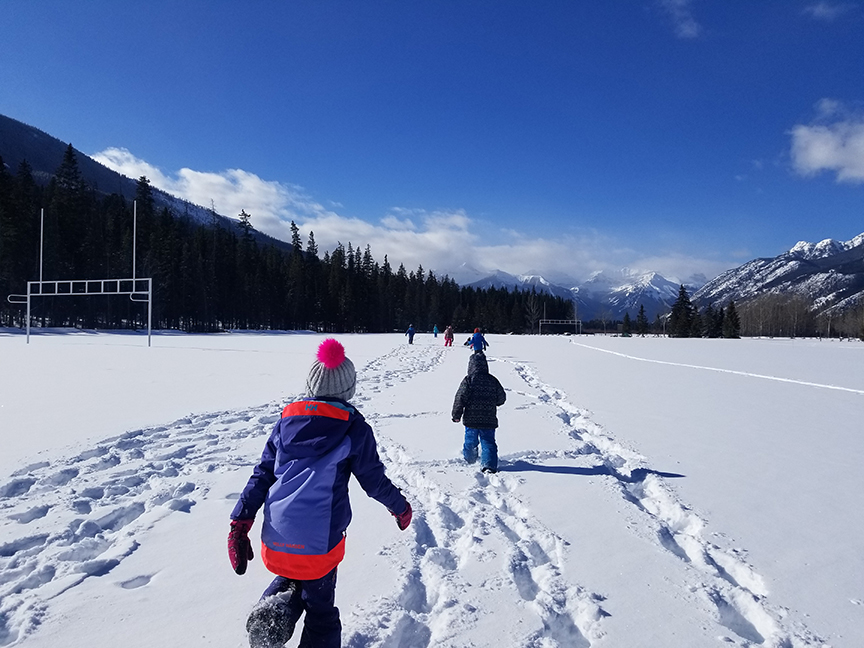 children walking in snow covered football field