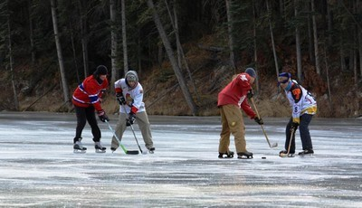 Four Men Playing Hockey on a Lake
